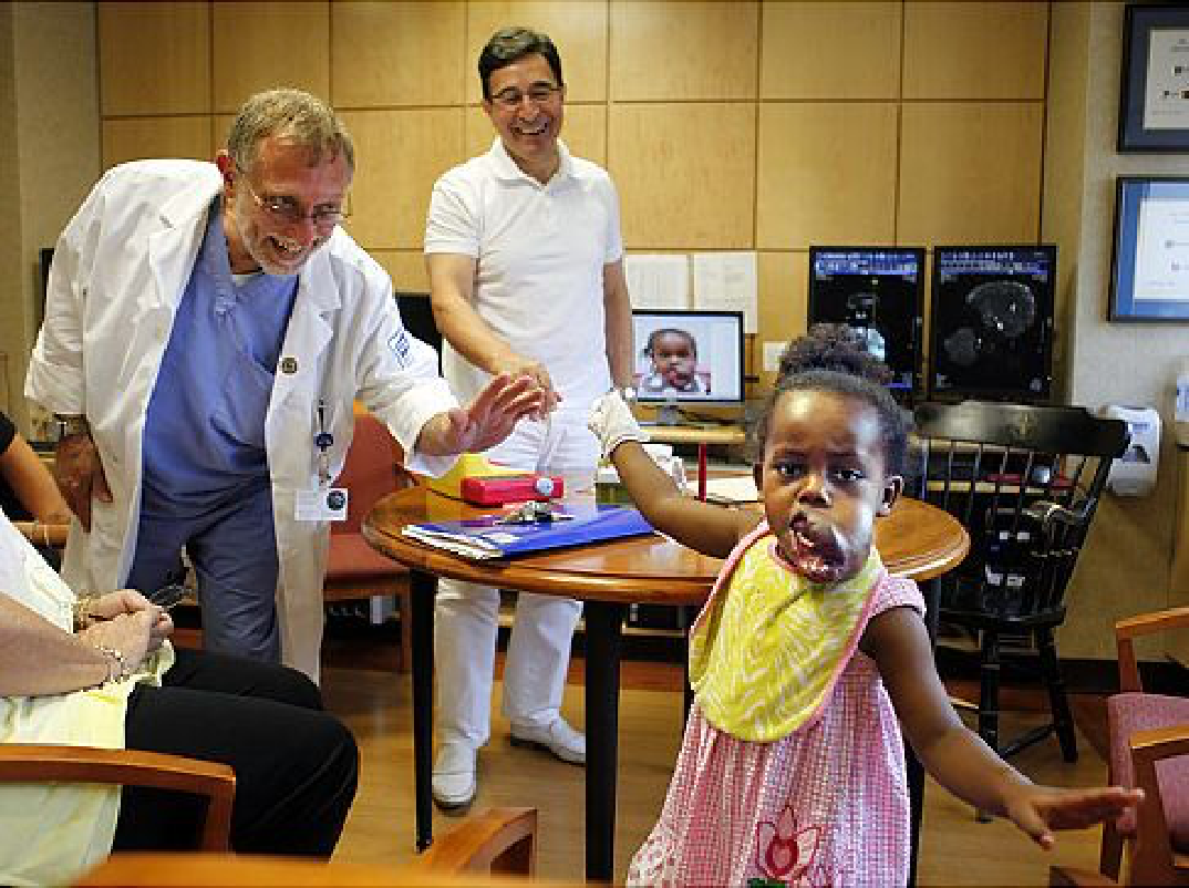 Dr. Alex Berenstein and Dr. Milton Waner with their little girl patient.